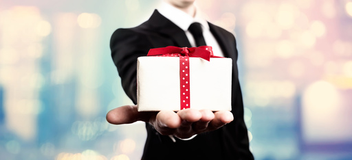 Businessman presenting a gift box